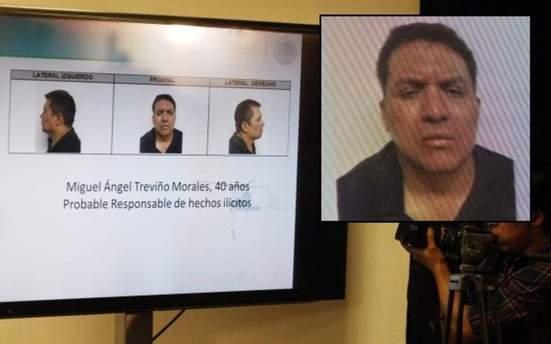 A cameraman films a screen showing photographs of Miguel Angel Trevino during a news conference in Mexico City